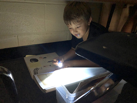 student reading by flashlight
