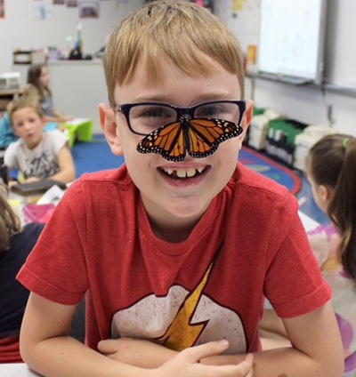 student with butterfly on his nose