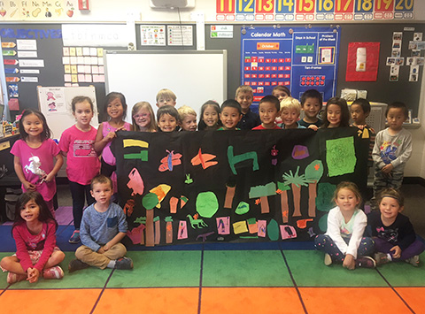 students with rainforest mural