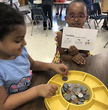 students with coins and a card