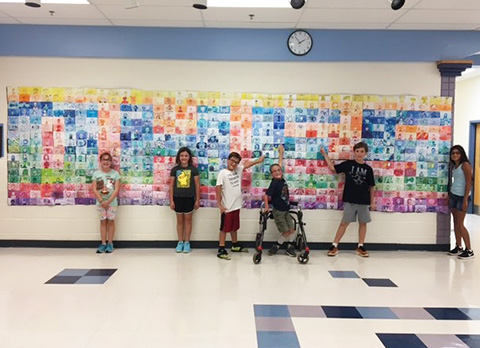 students with self-portrait mural