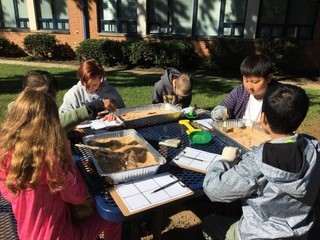 students excavating artifacts