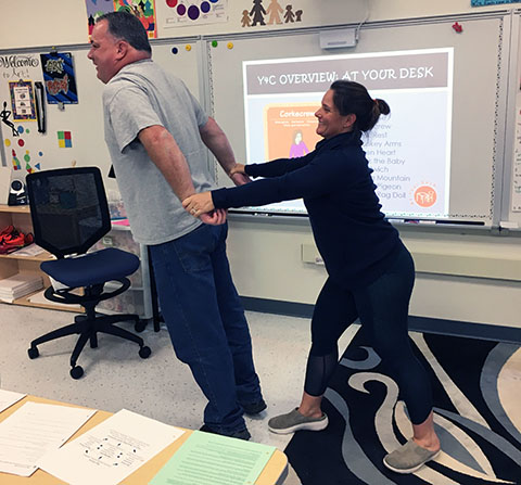teacher stretching colleague
