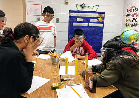 students reacting to science experiment