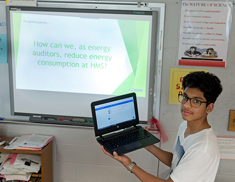 Herndon MS student with laptop and presentation on energy conservation