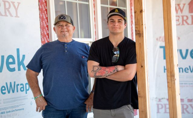 Meinert and Shane outside a home under construction in Spring Village Estates.