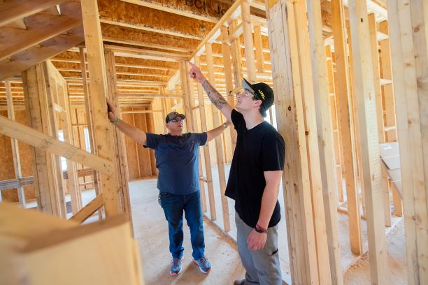 Instructor Ron Meinert reviewing building techniques with recent graduate Shane Bhatti at a home under construction at Spring Village Estates.