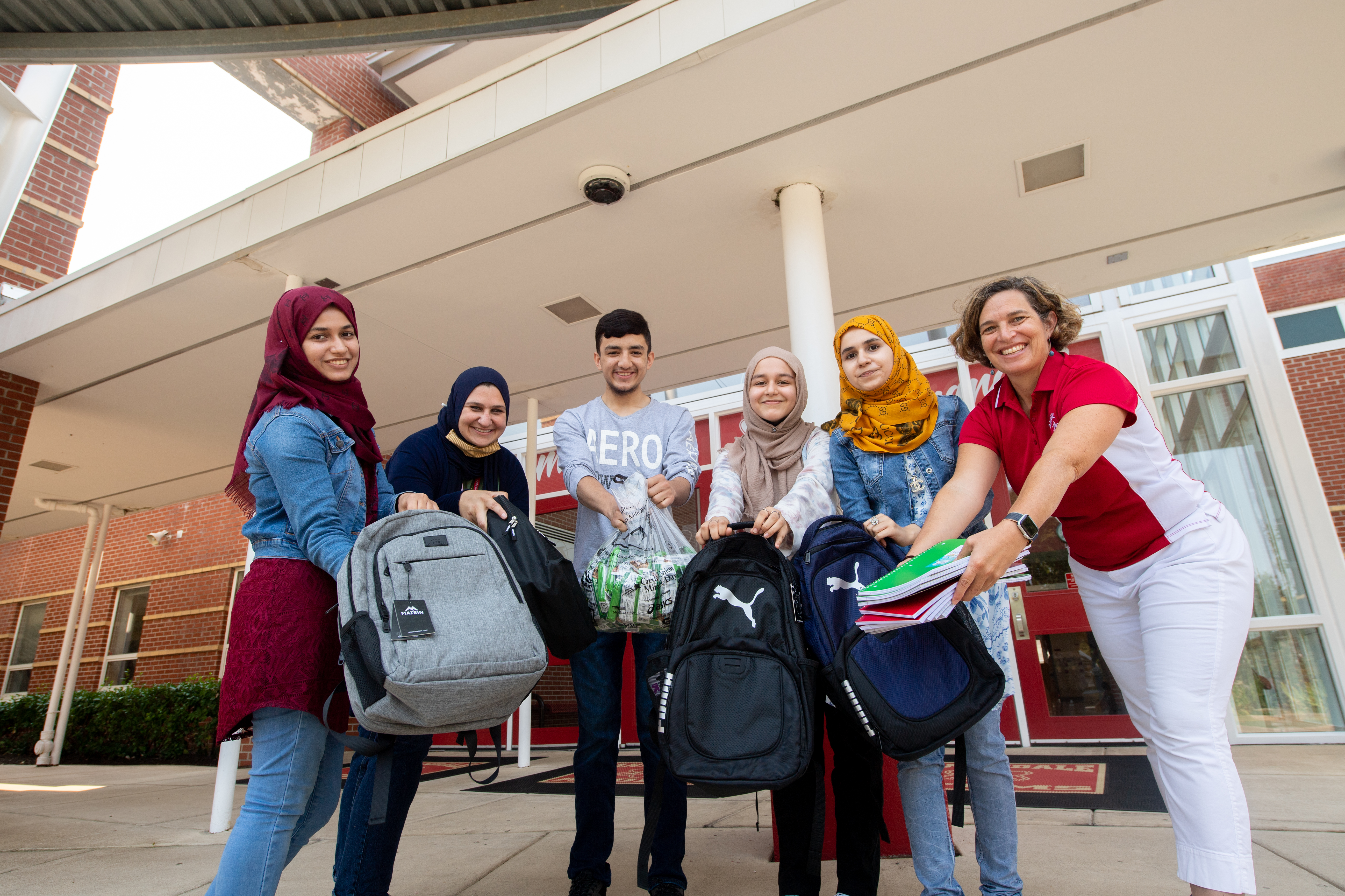 Annandale High Assistant Principal Sarah Eqab, English for Speakers of Other Languages Department Chairwoman Meredith Hedrick, and AHS students who came to the U.S. from Afghanistan over the past six years show backpacks and other supplies they've gathered to donate to newly arrived Afghan refugee students.