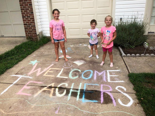 "students with ""Welcome Teachers"" in chalk on driveway"