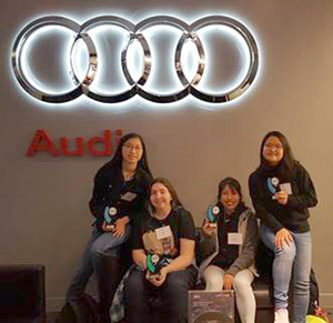 four students with Audi logo