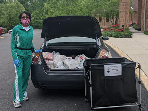 teacher with trunk full of donated items