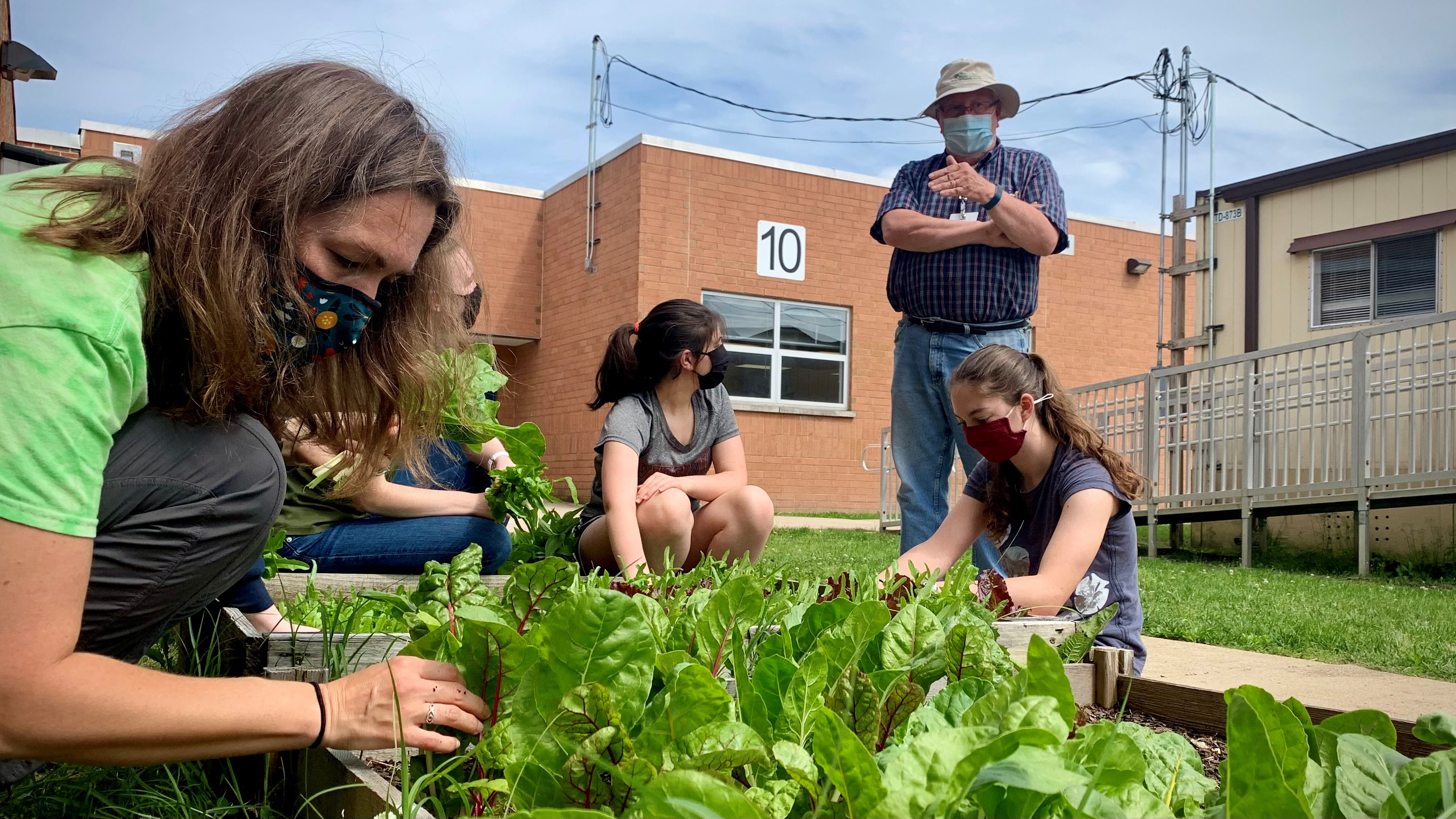 Master Gardener Tony Makara guides students as they weed and harvest.