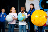 Students holding planets