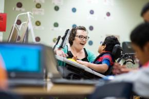 A teacher is smiling at a student in a wheelchair who is using assistive technology