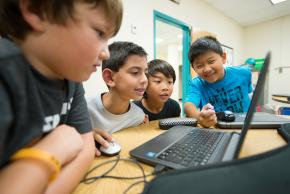 A group of boys is working together on solving measurement problems on a computer.
