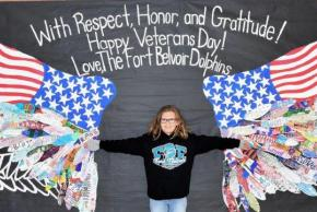 Female student standing between eagle wings on wall honoring veterans