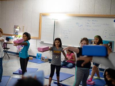 Students concentrate on steady breathing while balancing blocks.