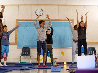 Students practice mountain pose while listening to messages of calmness and mindfulness.