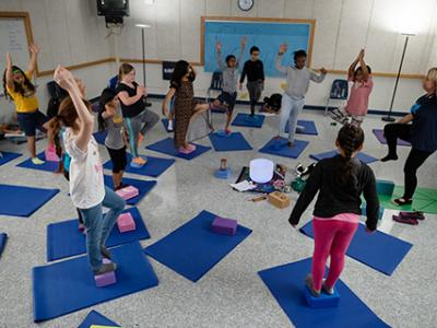Tupy uses yoga-inspired poses, like tree pose, to help center students.