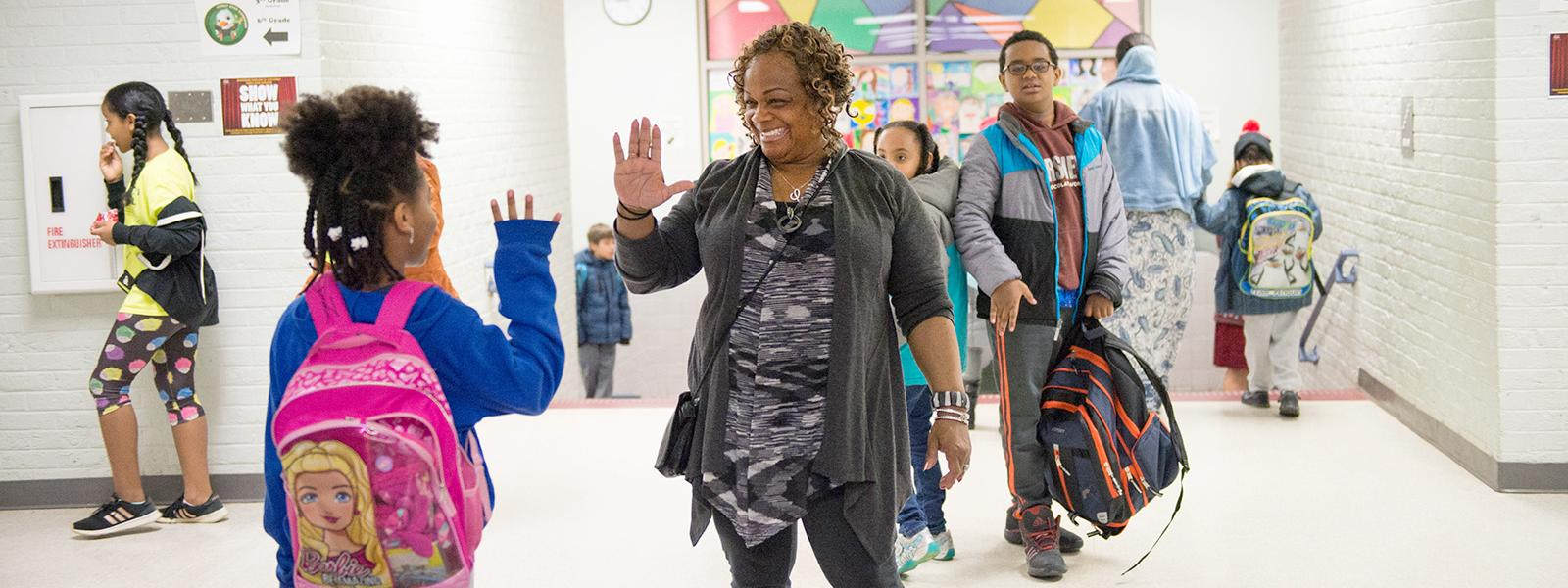 Instructional assistant Laverne Carter greets students with a big smile and a high five when they arrive at Forest Edge Elementary School.