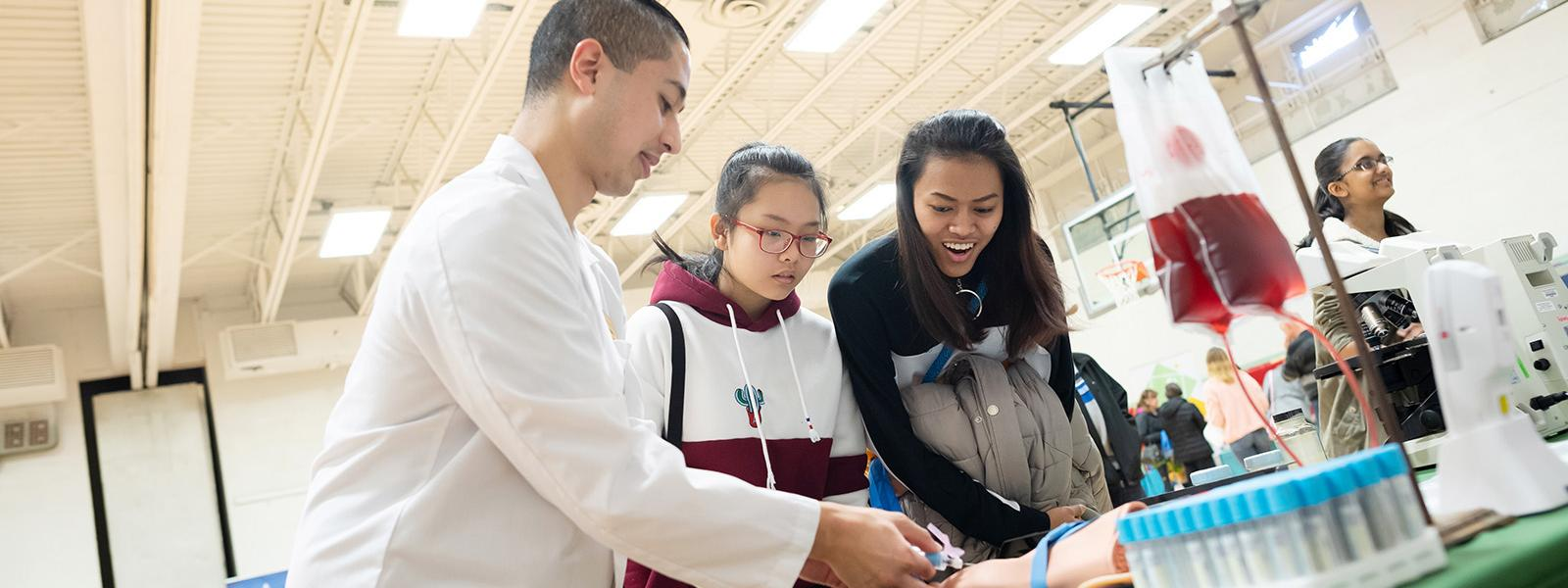 Falls Church Academy health sciences students observe a demonstration at a health care college and career fair.