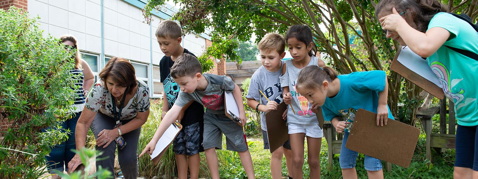 Students get a close look at pond inhabitants in the National Wildlife Federation Certified Schoolyard Habitat at Flint Hill Elementary School during a science lesson.