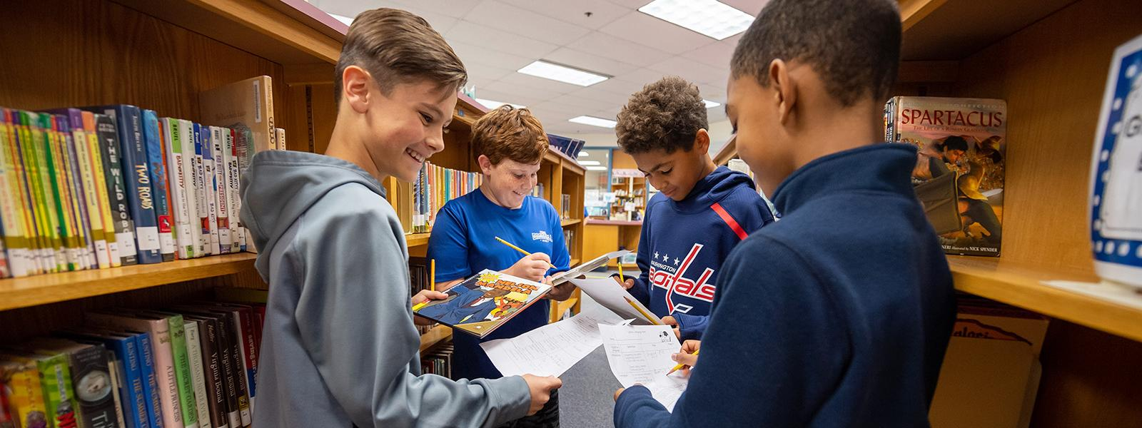 These Sangster Elementary School classmates exhibit communication and collaboration skills—attributes of Portrait of a Graduate—while working on an assignment in the library.