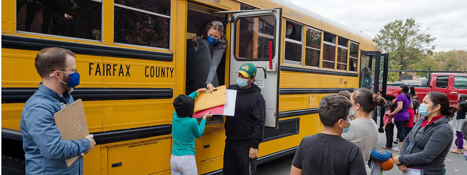 Woodburn Elementary School students receive books, materials, and pumpkins during a bus drop in their neighborhood.
